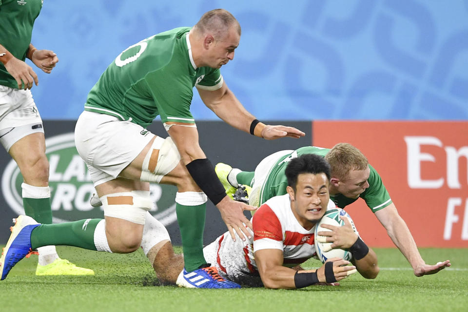 Japan's Kenki Fukuoka, bottom, scores a try against Ireland's defense during the Rugby World Cup Pool A game at Shizuoka Stadium Ecopa between Japan and Ireland in Shizuoka, Japan, Saturday, Sept. 28, 2019. (Tsuyoshi Ueda/Kyodo News via AP)