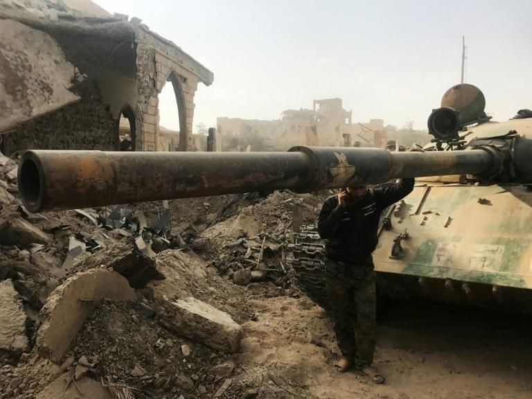 A member of Syrian pro-government forces stands next to a tank in the eastern city of Deir Ezzor during an operation against Islamic State group jihadists on November 4, 2017
