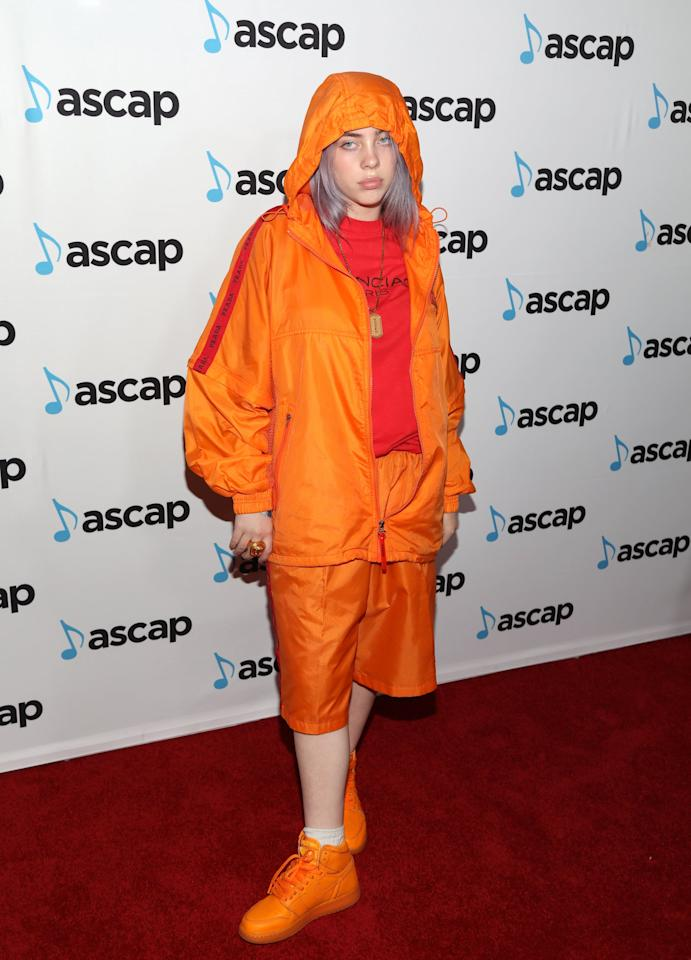 "<p>Billie is the queen of monochromatic ensembles. Case in point: her orange get-up for the 2018 ASCAP Pop Music Awards red carpet. We can't think of a more functional and comfy outfit to wear on <a class=""sugar-inline-link ga-track"" title=""Latest photos and news for Halloween"" href=""https://www.popsugar.com/Halloween"" target=""_blank"" data-ga-category=""Related"" data-ga-label=""https://www.popsugar.com/Halloween"" data-ga-action=""&lt;-related-&gt; Links"">Halloween</a>.</p> <p><strong>What to wear: </strong>Knee-length orange gym shorts and an orange t-shirt, with a matching windbreaker overtop. Bonus points if you also have a pair of orange sneakers handy. </p>"