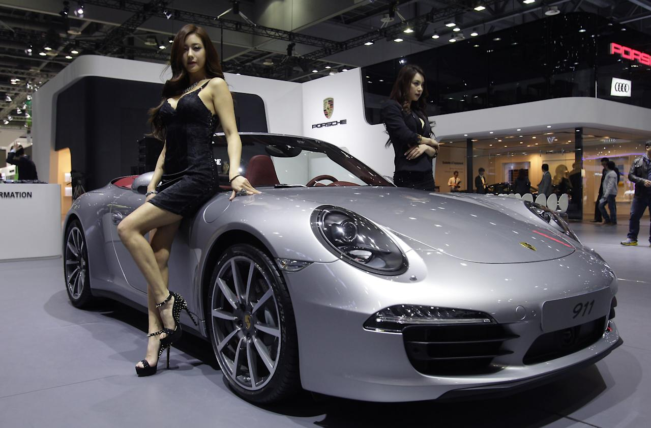 GOYANG, SOUTH KOREA - MARCH 28:  Models pose next to a Porsche 911 at the Seoul Motor Show 2013 on March 28, 2013 in Goyang, South Korea. The Seoul Motor Show 2013 will be held in March 29-April 7, featuring state-of-the-art technologies and concept cars from global automakers. The show is its ninth since the first one was held in 1995. About 384 companies from 14 countries, including auto parts manufacturers and tire makers, will set up booths to showcase trends in their respective industries, and to promote their latest products during the show.  (Photo by Chung Sung-Jun/Getty Images)