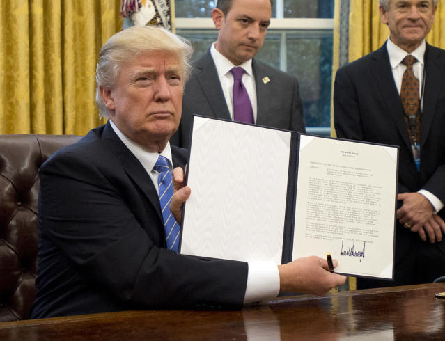 <p>U.S. President Donald Trump shows the Executive Order withdrawing the US from the Trans-Pacific Partnership (TPP) after signing it in the Oval Office of the White House in Washington, DC on Monday, January 23, 2017. (Ron Sachs – Pool/Getty Images) </p>