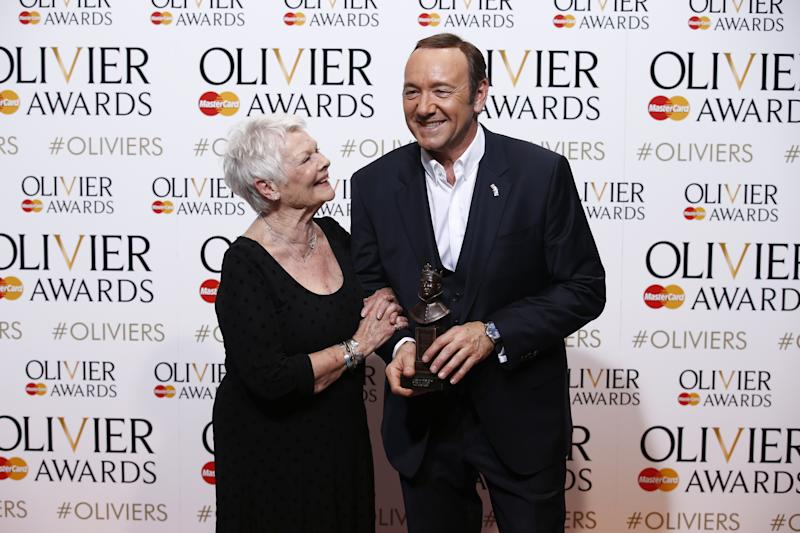 US actor, producer and director Kevin Spacey (R) poses with a special award recognising his contribution to British theatre during his tenure as Artistic Director of The Old Vic with British actress Judi Dench (L) during the Lawrence Olivier Awards for theatre at the Royal Opera House in central London on April 12, 2015. AFP PHOTO / JUSTIN TALLIS (Photo credit should read JUSTIN TALLIS/AFP/Getty Images)