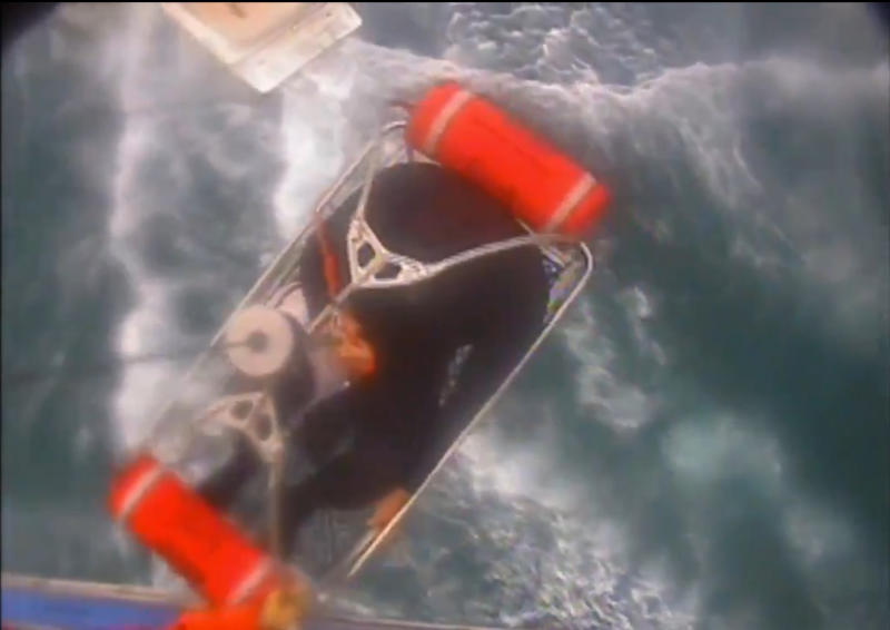 """In this Saturday, Dec. 21, 2019, video image released by the U.S. Coast Guard shows a man, wearing a full-body wetsuit, being hoisted up from the boat into the helicopter near Santa Rosa Island, one of the Channel Islands in Southern California. A shark reportedly bit a surfer Saturday afternoon in a """"truly terrifying situation,"""" the Coast Guard said. The 37-year-old man had been surfing near Santa Rosa Island, one of the Channel Islands, during the attack, according to a news release. (U.S. Coast Guard Los Angeles via AP)"""