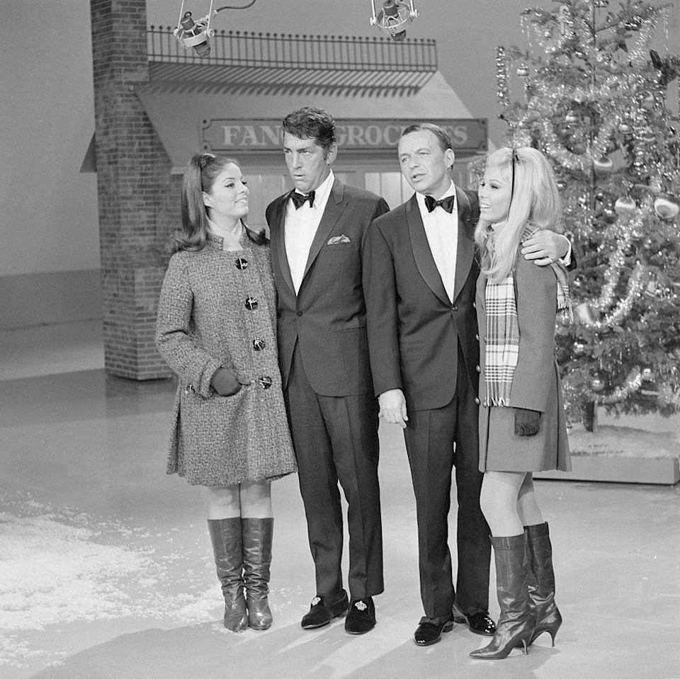 <p>Longtime pals, Dean Martin and Frank Sinatra, are joined by their daughters, Gail Martin and Nancy Sinatra, for a Christmas segment on <em>The Dean Martin Show. </em>Afterwards other members of their families joined in on the holiday fun.</p>