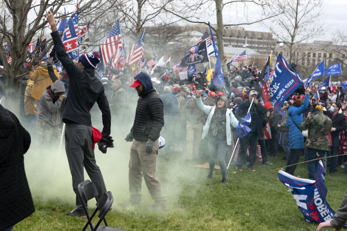 FILE - In this Jan. 6, 2021, file photo, supporter of President Donald Trump protest as U.S. Capitol Police officers shoot tear gas at demonstrators outside of the U.S. Capitol in Washington. Far-right social media users for weeks openly hinted in widely shared posts that chaos would erupt at the U.S. Capitol while Congress convened to certify the election results. (AP Photo/Jose Luis Magana)