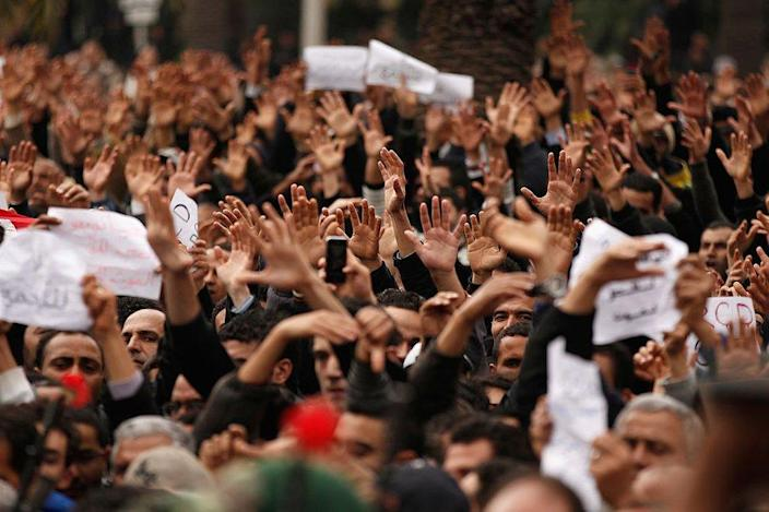 Tunisian demonstrators gesture with their hands calling to the army to pull down the Constitutional Democratic Rally (RCD) party headquarters sign on January 20, 2011 in Tunis, Tunisia.
