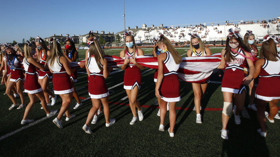 Herriman cheerleaders carry the American flag before the start of a high school football game between Davis and Herriman on Thursday, Aug. 13, 2020, in Herriman, Utah. Utah is among the states going forward with high school football this fall despite concerns about the ongoing COVID-19 pandemic that led other states and many college football conferences to postpone games in hopes of instead playing in the spring. (AP Photo/Rick Bowmer)