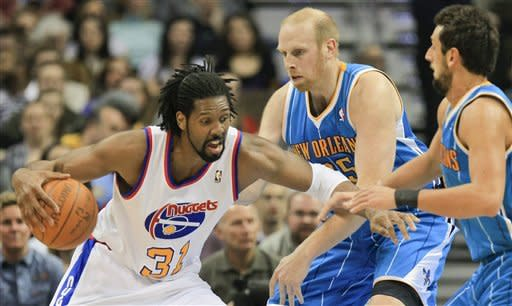 Denver Nuggets center Nene Hilario, left, drives through New Orleans Hornets' center Chris Kaman, center, and Marco Belinelli, right, during the first quarter of an NBA basketball game Friday, March 9, 2012 in Denver. (AP Photo/Barry Gutierrez)