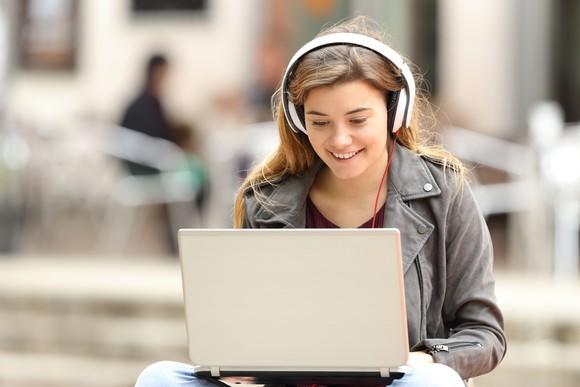 A girl listens to music using headphones.