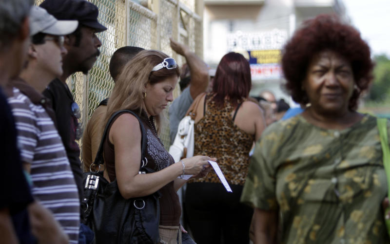 """A woman reads a passport application form as she waits in line outside an immigration office in Havana, Cuba, Monday, Jan. 7, 2013. A Cuban doctor says the Caribbean nation is eliminating longstanding restrictions on health care professionals' overseas travel as part of a broader migration reform. The doctor says hospital directors met Saturday with Health Minister Roberto Morales and were told of the new policy, effective Jan. 14. For many years Cuban physicians have been limited in their ability to travel or had to undergo cumbersome bureaucratic procedures. But now they are supposed to be treated """"like any other citizen"""" when it comes to traveling abroad. (AP Photo/Franklin Reyes)"""