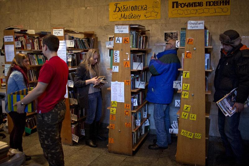 In this photo taken on Thursday, Feb. 6, 2014, Ukrainian protesters look at books organized on shelves in an improvised library set inside the Ukrainian House in Kiev. When the fervor flags for the protesters in Ukraine's capital and they want to get away from the barricades for a little while, many of them are heading to an improvised library in one of the buildings seized by demonstrators. (AP Photo/Emilio Morenatti)