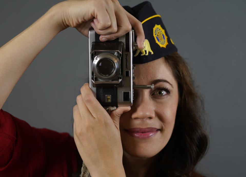 """In this June 30, 2021, Los Angeles-based producer, actress and Marine Corps veteran Jennifer Brofer poses with a vintage Voigtlander Vitessa film camera gifted by her grandfather at her apartment in Los Angeles. Brofer will never forget the loud, popping noise. It was on a hot July afternoon in 2010 when her convoy rolled over an IED on a road in Helmand Province four months into her deployment to Afghanistan. Her heart froze as she and her fellow Marines stopped and realized what had occurred. But what followed were only the sounds of daily life. Brofer, 38, who now works in the film industry in Hollywood, said she feels proud to have served """"shoulder-to-shoulder with my male marine counterparts"""" in a time of war. (AP Photo/Damian Dovarganes)"""