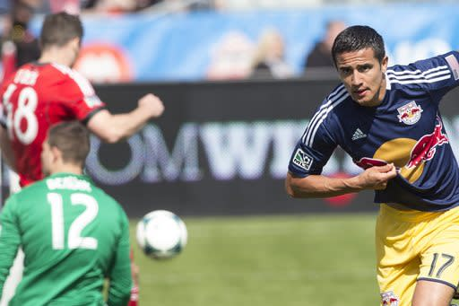 New York Red Bulls' Tim Cahill, right, reacts after scoring his team's winning goal past Toronto FC 's Joseph Bendik (12) during the second half of an MLS soccer game in Toronto on Saturday, April 27, 2013. (AP Photo/The Canadian Press, Chris Young)