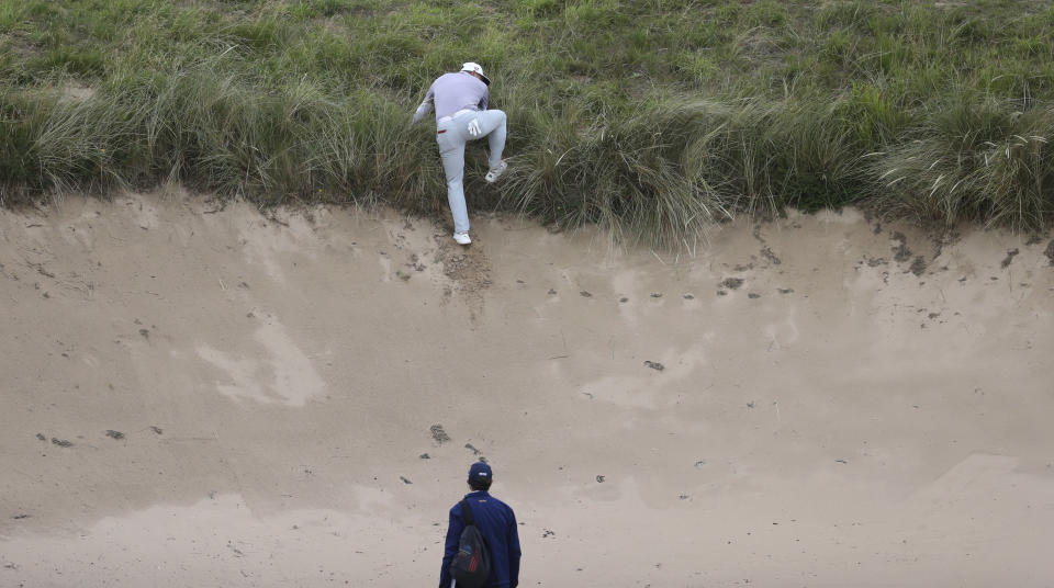 Gary Woodland of the United States attempts to find a sure footing to play his ball that is on the top edge of a bunker on the 7th hole during the first round of the British Open Golf Championships at Royal Portrush in Northern Ireland, Thursday, July 18, 2019.(AP Photo/Peter Morrison)