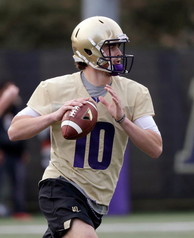 FILE - In this March 28, 2018, file photo, Washington quarterback Jacob Eason readies a pass at the first practice of spring football for the NCAA college team, in Seattle. Eason knew his opportunity at Georgia was going to be limited if he remained with the Bulldogs. So he transferred home to Washington, even if it means he has to spend a year as a spectator. (AP Photo/Elaine Thompson, File)