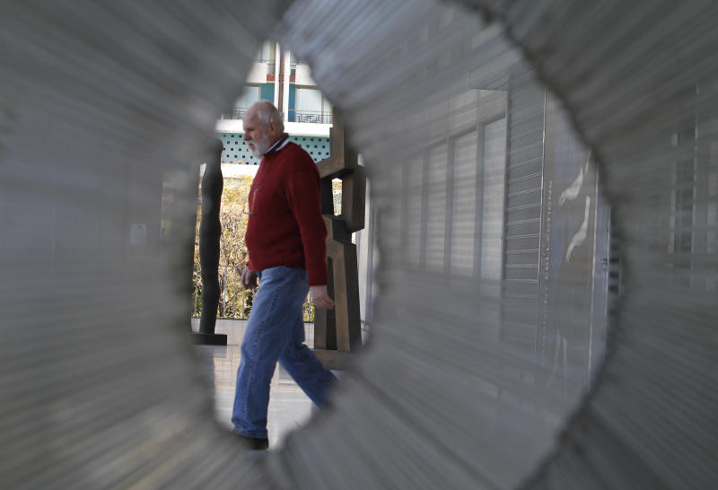 A worker of National Art Gallery exits the building as seen through an outdoor sculpture in Athens, on Monday, Jan. 9, 2011. Greek police say thieves have broken into the country's biggest art museum and stolen two paintings. (AP Photo/Thanassis Stavrakis)