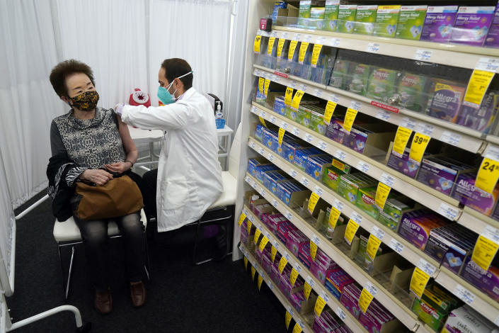 Pharmacist Todd Gharibian, right, administers a dose of the Moderna COVID-19 vaccine to Toshiko Sugiyama, left, at a CVS Pharmacy branch Monday, March 1, 2021, in Los Angeles. (AP Photo/Marcio Jose Sanchez)
