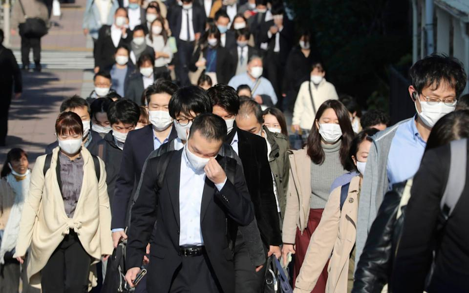 Commuters wearing face masks to protect against the spread of the coronavirus walk on a street in Tokyo - AP