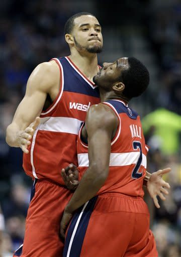 Washington Wizards center JaVale McGee, left, celebrates with John Wall, right, after McGee dunked on an assist from Wall during the first half of an NBA basketball game against the Dallas Mavericks Tuesday, March 13, 2012, in Dallas. (AP Photo/Tony Gutierrez)