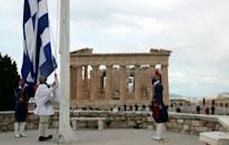 Members of the Presidential Guard raised the Greek flag in front of the Parthenon temple atop of Acropolis Hill during the ceremony