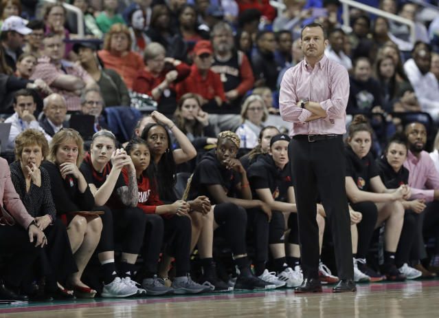 Louisville head coach Jeff Walz, right, and players watch during the late moments of the second half of an NCAA college basketball game against Notre Dame in the championship of the Atlantic Coast Conference women's tournament in Greensboro, N.C., Sunday, March 10, 2019. Louisville lost to Notre Dame 99-79. (AP Photo/Chuck Burton)