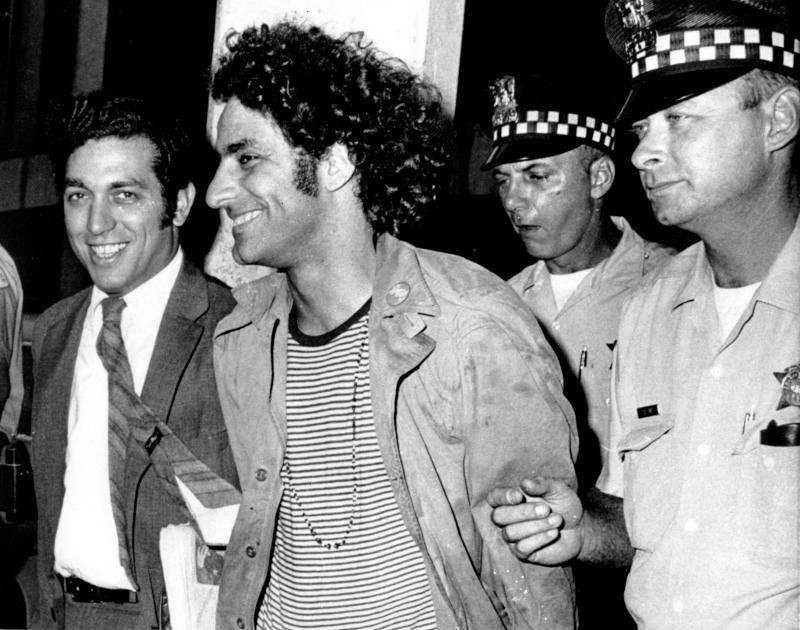 Abbie Hoffman, leader of the Youth International Party known as the Yippies, is escorted by police after his arrest at O'Hare Field in Chicago upon his arrival from New York on Sept. 17, 1968. He was sought for not appearing in court on Sept. 6 to answer charges of disorderly conduct and resisting arrest. Police said a switchblade knife and a knife with a four-inch blade was found on Hoffman, who was then booked on charges of unlawful use of weapon. At left is his attorney Gerald B. Lafcourt. (AP Photo)