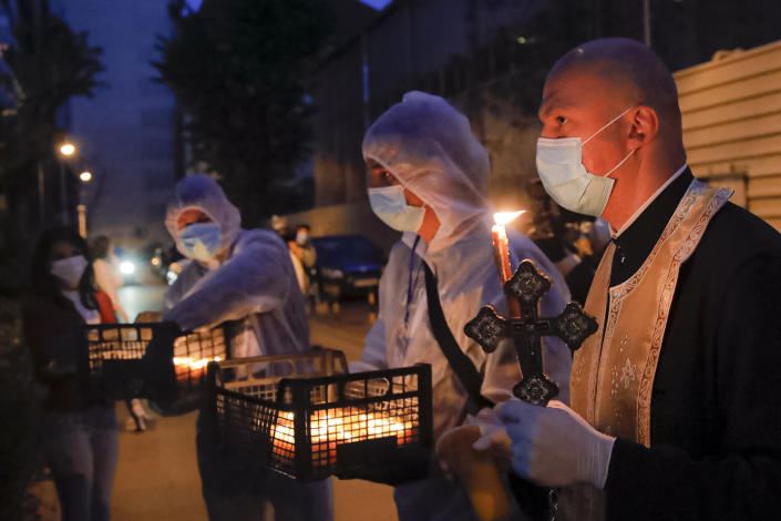 A priest distributes holy light to households during the coronavirus pandemic in Bucharest, Romania, Saturday, April 18, 2020. Priests accompanied by volunteers distributed the holy light ahead of the usual time, at midnight, as people observed the interdiction to join religious celebrations in the week leading to the Orthodox Easter, imposed across Romania as authorities try to limit the spread of the COVID-19 infections. (AP Photo/Vadim Ghirda)