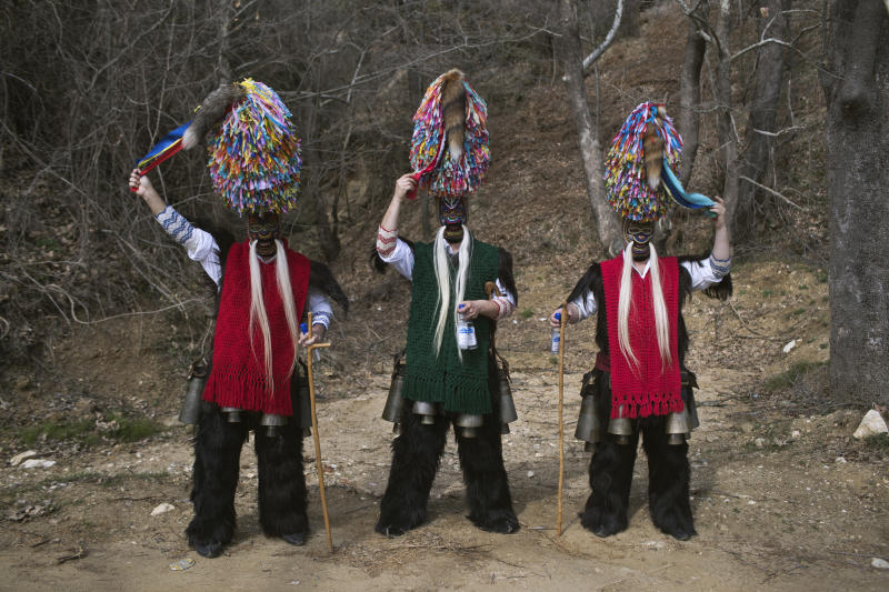 In this Monday March 11, 2019 photo, men wearing goat hides with bells around their waist and masks that include a meter tall, ribbon-covered formation topped with a foxtail, also known as bell wearers, pose for a photo at the village of Sohos, northern Greece as they participate in a Clean Monday festival. Greek carnivals at this time of year can be modest but they showcase ancient rites and traditions as well as providing reminders to some bloody moments in the country's modern history. In northern Greece, two of the most celebrated carnival customs are found in the mountain town of Sochos, and in Naoussa. (AP Photo/Petros Giannakouris)