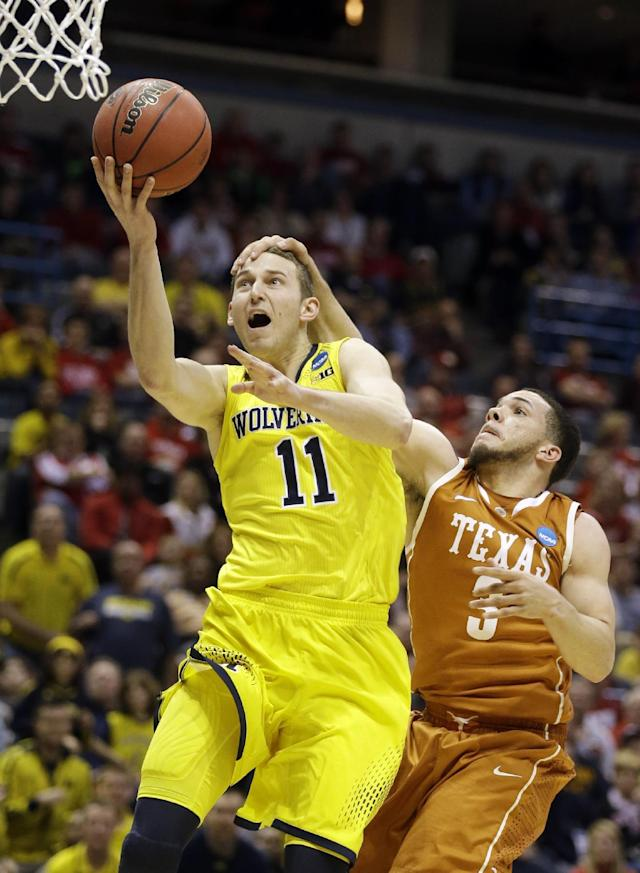 Michigan guard Nik Stauskas (11) is fouled by Texas guard Javan Felix (3) during the second half of a third-round game of the NCAA college basketball tournament Saturday, March 22, 2014, in Milwaukee. (AP Photo/Jeffrey Phelps)