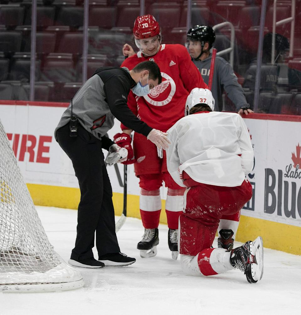A Detroit Red Wings trainer helps an injured Evgeny Svechnikov during the third period in a scrimmage Tuesday, Jan. 5, 2021 at Little Caesars Arena in Detroit.