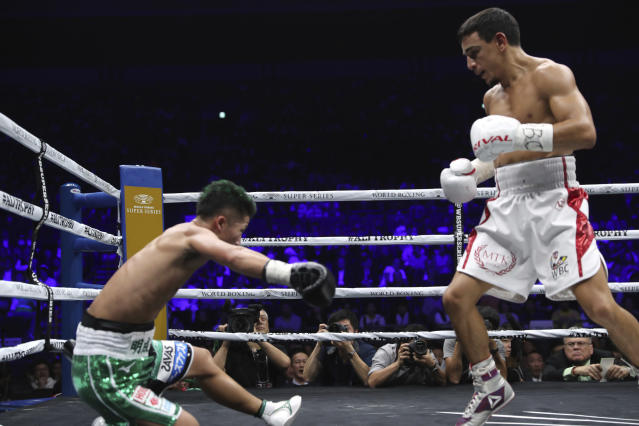 France's Nordine Oubaali, right, looks at Japan's Takuma Inoue falling down a mat in the fourth round of their WBC world bantamweight title match in Saitama, Japan, Thursday, Nov. 7, 2019. Oubaali defeated Inoue by a unanimous decision. (AP Photo/Toru Takahashi)