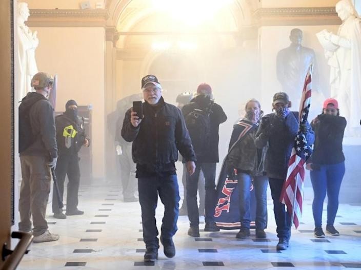 Supporters of US President Donald Trump enter the US Capitol as tear gas fills a corridor
