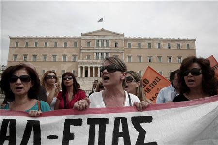Protesters shout slogans during a rally by high school teachers against layoffs in their sector in front of the parliament in Athens