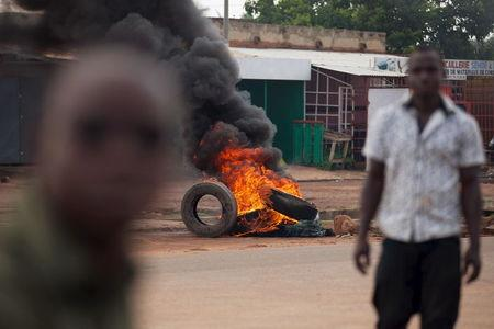 Men walk in front of a burning barricade set up by anti-coup protesters in Ouagadougou, Burkina Faso, September 21, 2015. REUTERS/Joe Penney