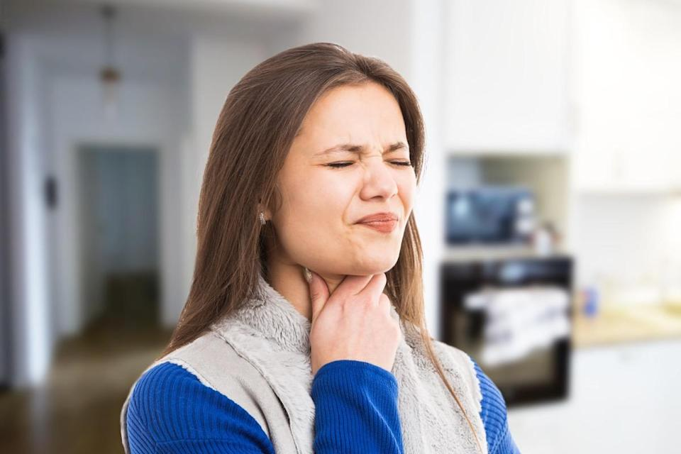 woman experiencing strong throat ache