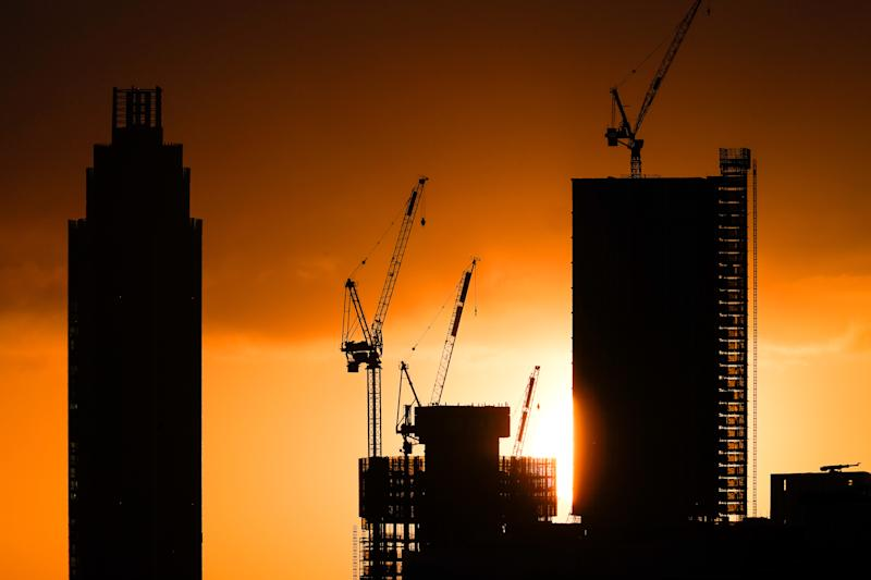 The sun rises behind tower blocks under construction in London as the clocks move forward an hour to British Summer Time (BST).