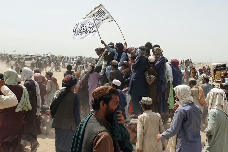 Taliban supporters wave flags as they drive through the Pakistani border town of Chaman after the insurgents captured Spin Boldak on the Afghan side of the frontier