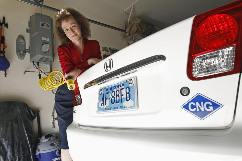 Connie Jones with natural gas powered Honda Civic and natural gas home refueling station located on garage wall of her home in Chandler