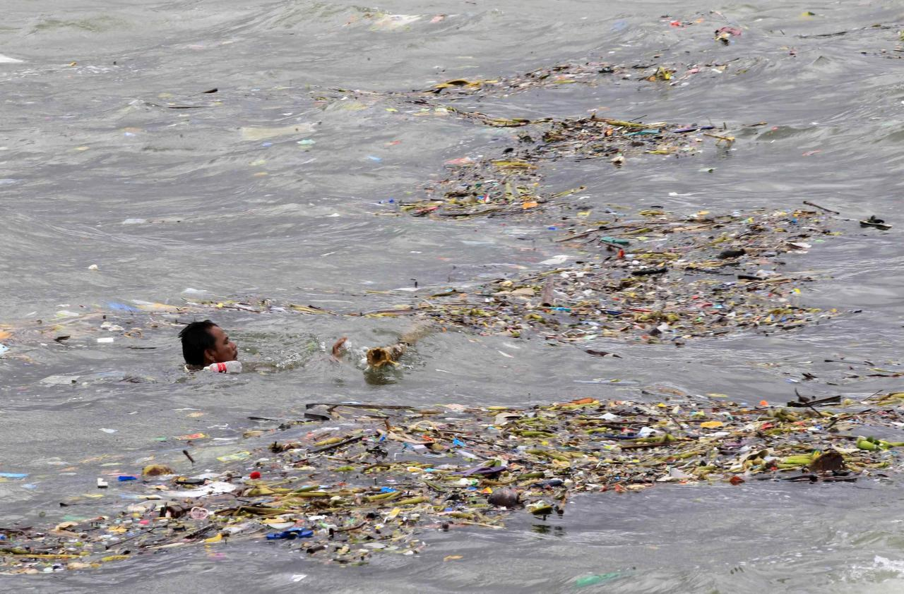 A man swims to gather recyclable materials amidst debris brought by Typhoon Rammasun, (locally named Glenda) along the seashore of the coastal town of Baseco compound, metro Manila July 17, 2014. The Philippines set to work clearing debris, reconnecting power and rebuilding flattened houses on Thursday after the typhoon swept across the country killing 38 people, with at least eight missing, rescue officials said. REUTERS/Romeo Ranoco(PHILIPPINES - Tags: DISASTER ENVIRONMENT)