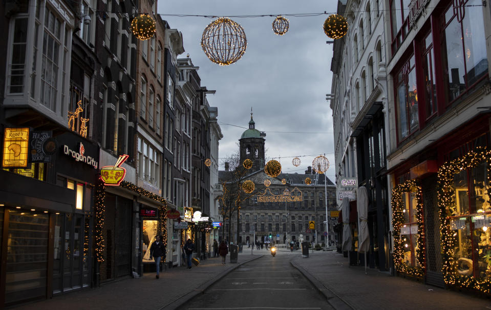 FILE- In this Thursday, Jan. 14, 2021, file photo, closed stores on Dam street and the Royal Palace on Dam Square, rear, are seen in Amsterdam. The Dutch government said Wednesday, Jan. 20, 2021, that it wants to impose a curfew as part of beefed-up restrictions to rein in the spread of new more contagious variants of the coronavirus that already accounts for at least one in every 10 Dutch infections. (AP Photo/Peter Dejong, File)