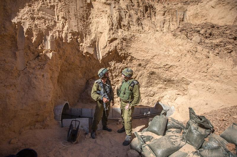 Israeli officers stand at the entrance to a tunnel said to have been used by Palestinian militants for cross-border attacks from the Gaza Strip on July 25, 2014 (AFP Photo/JACK GUEZ)
