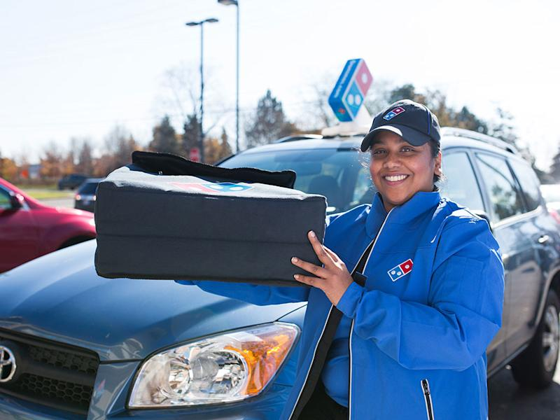 A Domino's Pizza employee holding pizza boxes beside her delivery vehicle.
