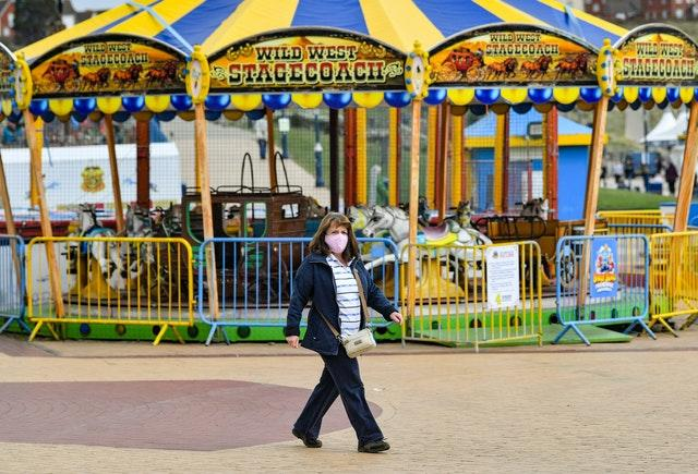 A woman walks past closed fairground rides on the seafront at Barry Island in the Vale of Glamorgan (Ben Birchall/PA)