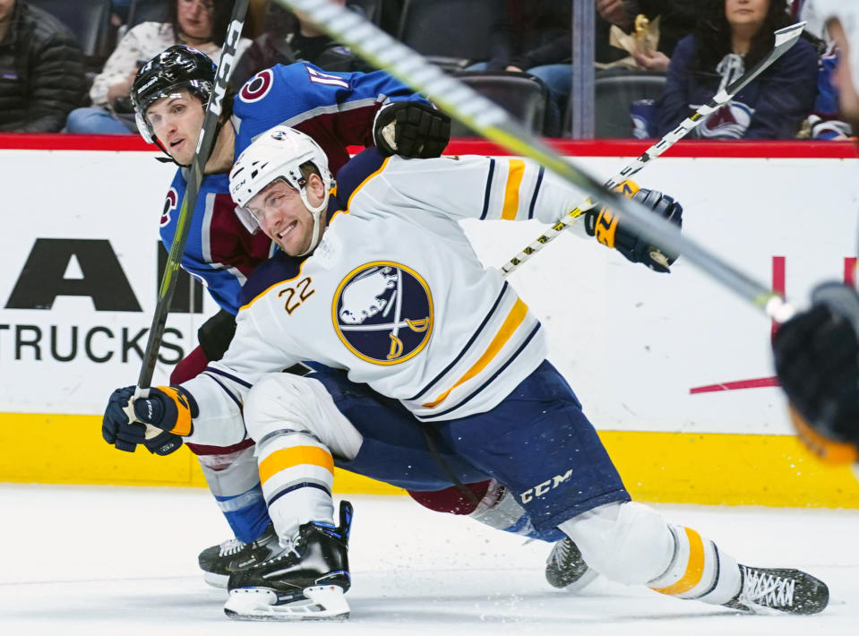 Colorado Avalanche center Alexander Kerfoot (13) drags down Buffalo Sabres center Johan Larsson (22) during the first period of an NHL hockey game Saturday, March 9, 2019, in Denver. (AP Photo/Jack Dempsey)