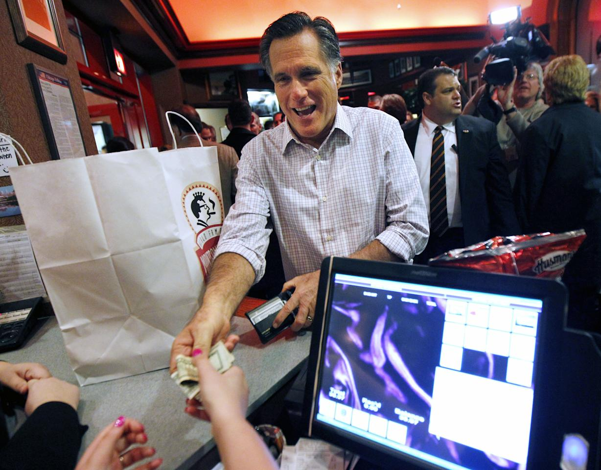 Republican presidential candidate, former Massachusetts Gov. Mitt Romney pays for his take-out order at the Montgomery Inn in Cincinnati, Saturday, March 3, 2012. (AP Photo/Gerald Herbert)