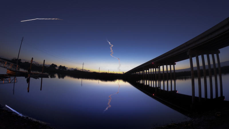 A United Launch Alliance Atlas V rocket streaks across the horizon at dawn in this view from the St. Johns River, east of Sanford, Fla., Friday, Dec. 20, 2019. The rocket was carrying Boeing's Starliner crew capsule toward the International Space Station on an unpiloted test flight and was visible along the U.S. east coast. (Joe Burbank/Orlando Sentinel via AP)