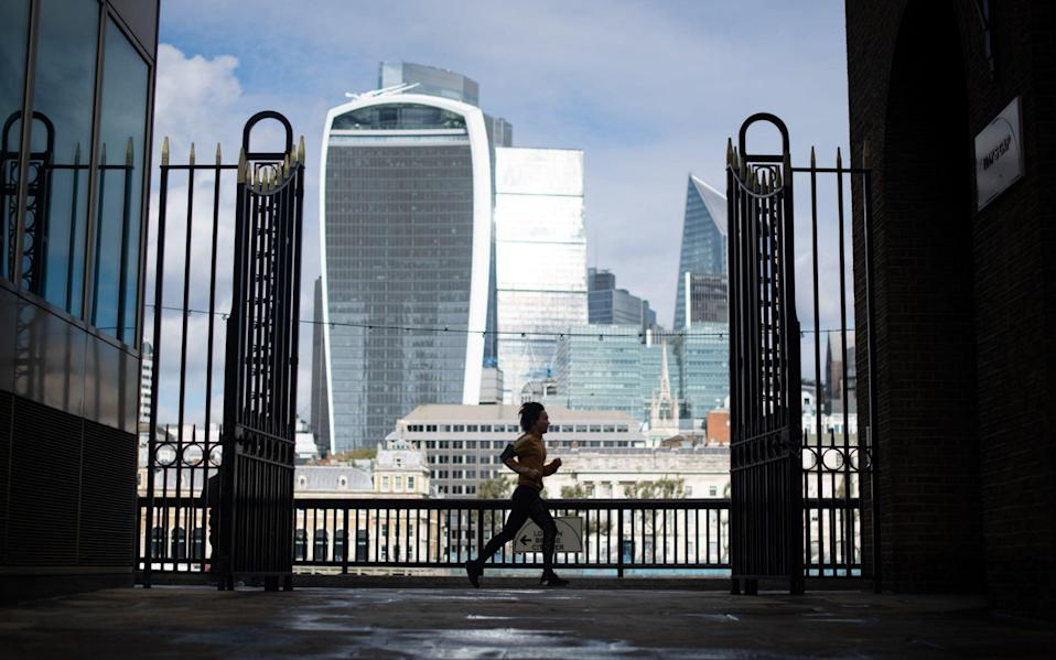 A jogger runs along the river Thames, passing skyscrapers in the City financial district of London - Dominic Lipinski/PA