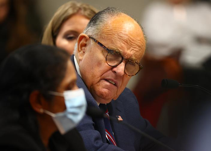 Rudy Giuliani listens to a Detroit poll worker during an appearance before the Michigan House Oversight Committee on Dec. 2 in Lansing. (Rey Del Rio/Getty Images)