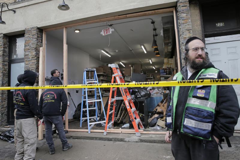 FILE - In this Wednesday, Dec. 11, 2019, file photo, people work to secure the scene of a shooting at a kosher supermarket in Jersey City, N.J. On Friday, Dec. 13, 2019, The Associated Press reported on photos circulating online incorrectly claiming to show the assailants involved in Tuesday's Jersey City gunbattle. The photos actually show Darius Bolden and Yasmin Tejada, who were connected to a separate murder case that dates back to August. (AP Photo/Seth Wenig)