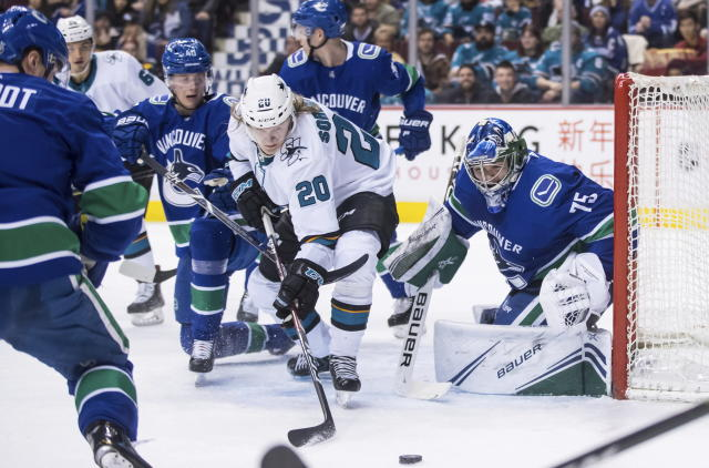 San Jose Sharks' Marcus Sorensen (20), of Sweden, reaches for the puck in front of Vancouver Canucks goalie Michael DiPietro (75) as Vancouver's Elias Pettersson (40), of Sweden, watches during the first period of an NHL hockey game in Vancouver, British Columbia, on Monday, Feb. 11, 2019. (Darryl Dyck/The Canadian Press via AP)